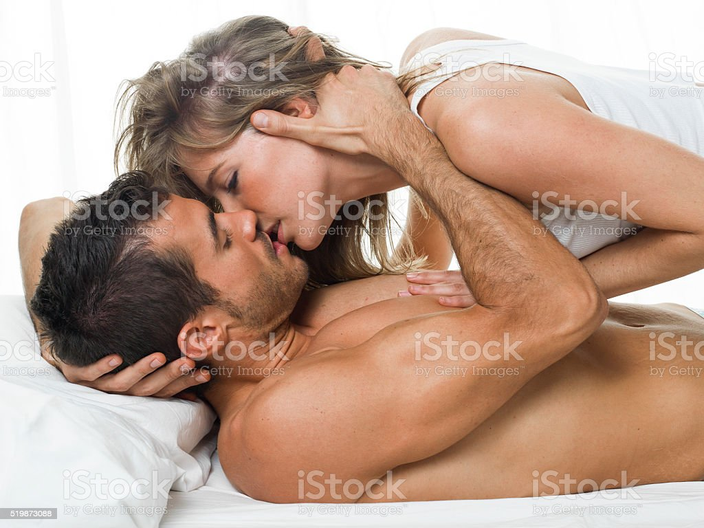 attractive couple in love under white bed sheets stock photo
