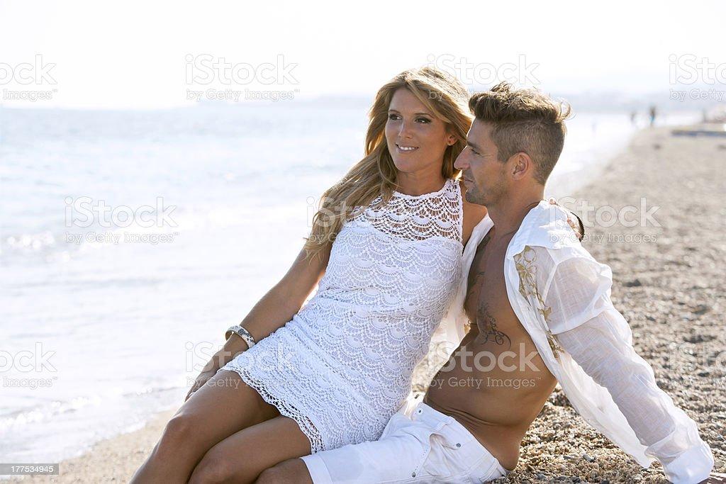 Attrayant couple en blanc assis sur la plage de galets. photo libre de droits