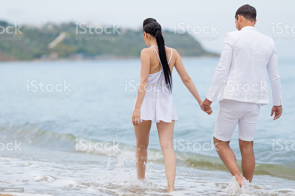 Attractive couple in white walking along waters edge, rear view stock photo
