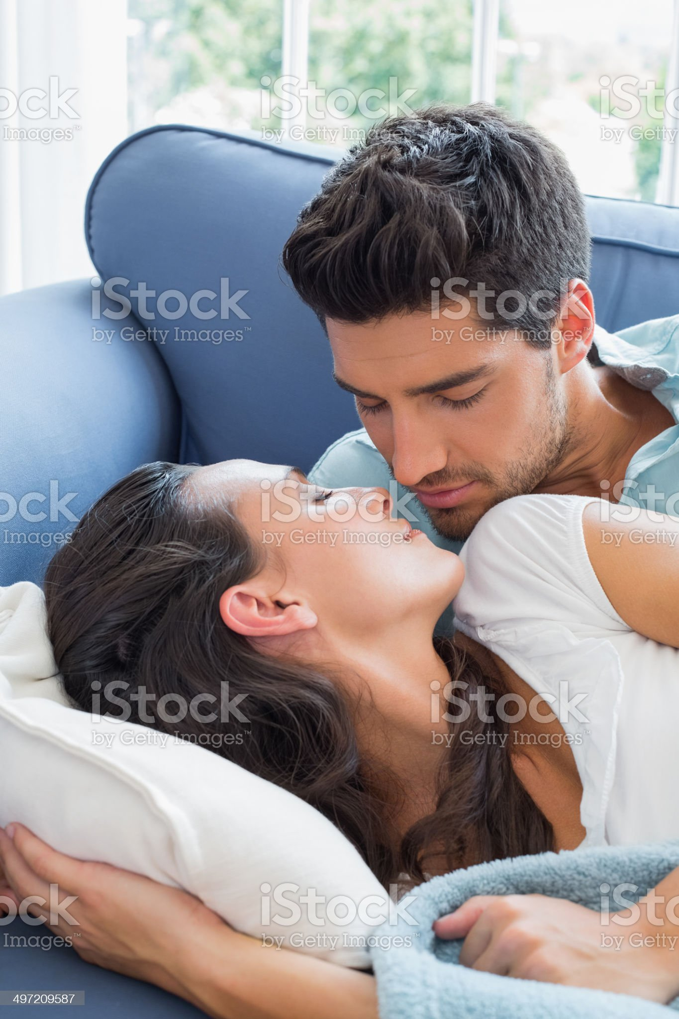 Attractive couple kiss while lying on sofa royalty-free stock photo