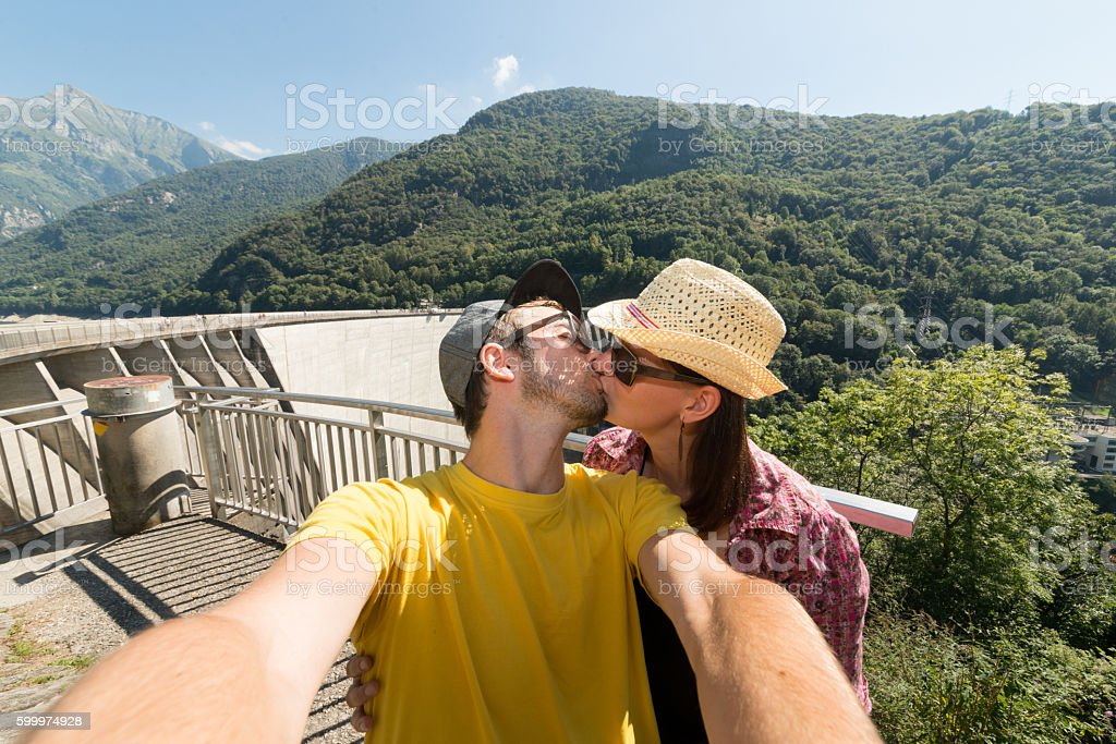 Attractive couple kissing infront famous dam stock photo