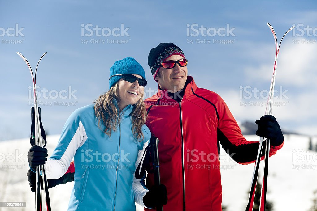 Attractive Couple Looking Away Holding Ski Gear royalty-free stock photo