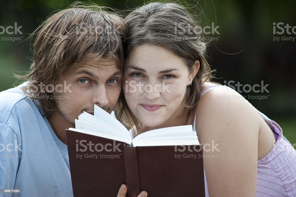 Attractive couple peers over a book royalty-free stock photo