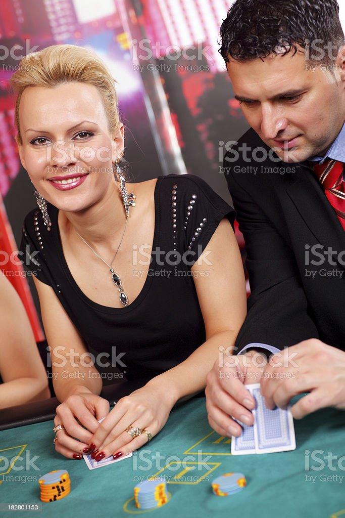 Attractive couple playing Blackjack in casino. stock photo