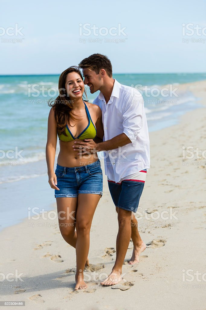 Attractive couple smiling and walking on the beach stock photo