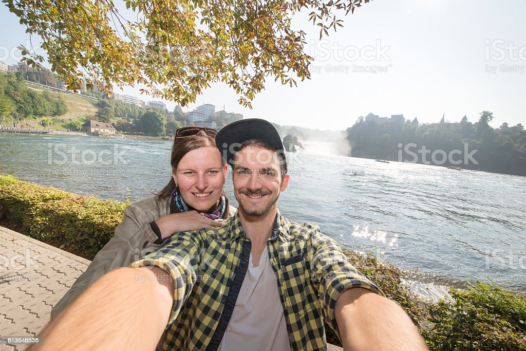 Attractive couple smiling infront rhinefall switzerland stock photo