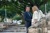 Attractive couple stand near stone staircase talking