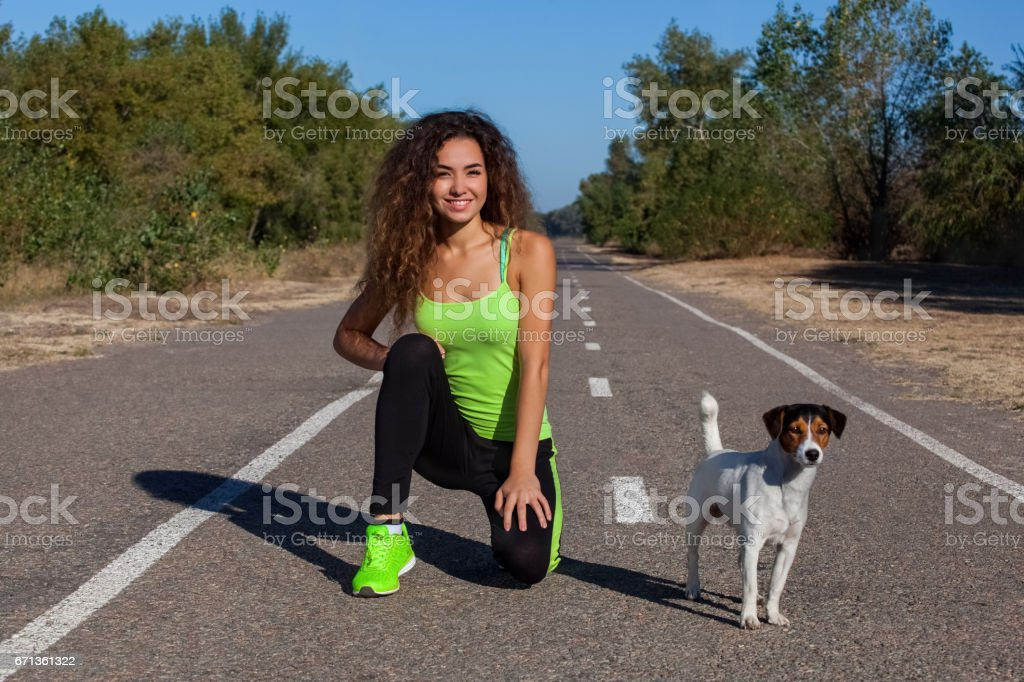 Attractive curly girl athlete doing morning exercises with her dog on the street stock photo