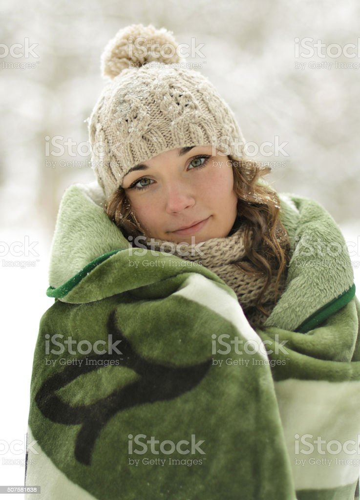 Attractive, cute, beautiful girl wrapped up warm plaid, blanket winter stock photo