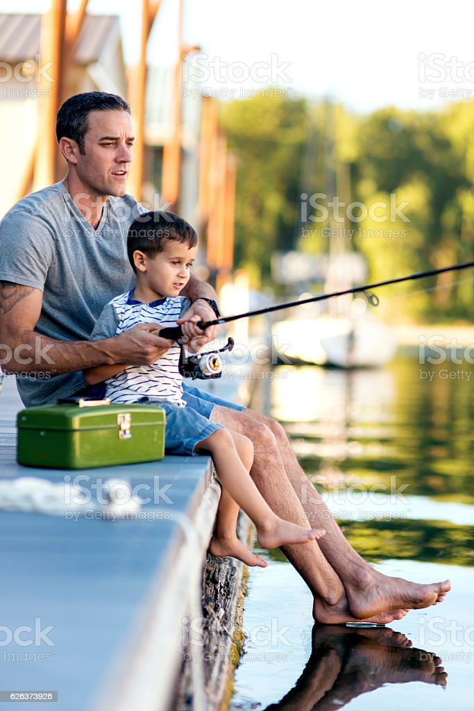 Attractive dad teaching his young boy how to fish stock photo