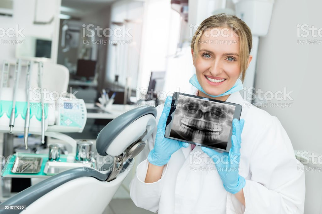 Attractive dentist showing dental x-ray on touchpad stock photo