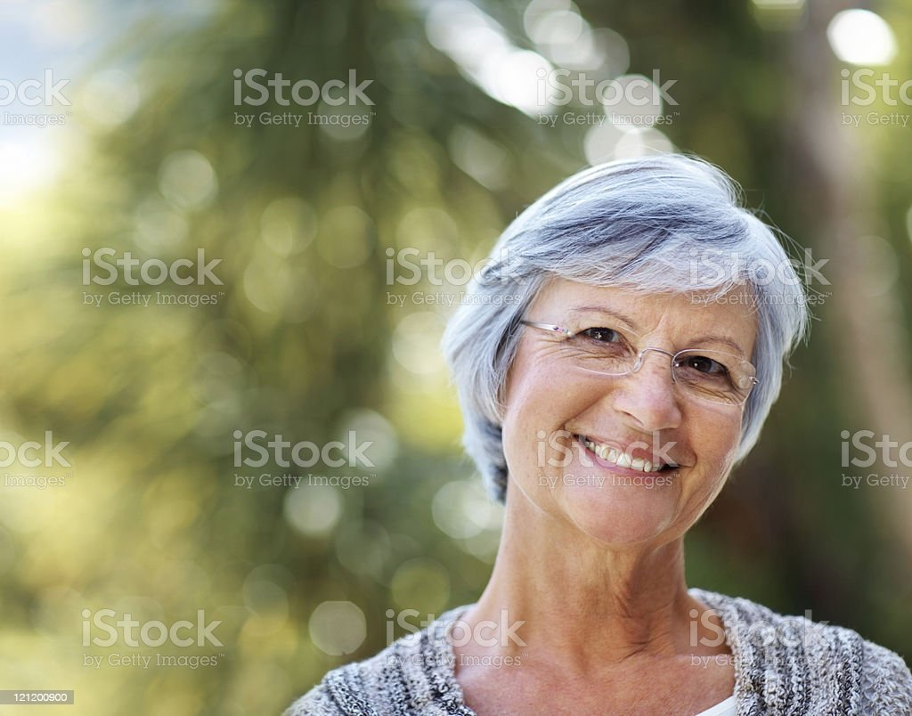Attractive elderly woman smiling in the park royalty-free stock photo