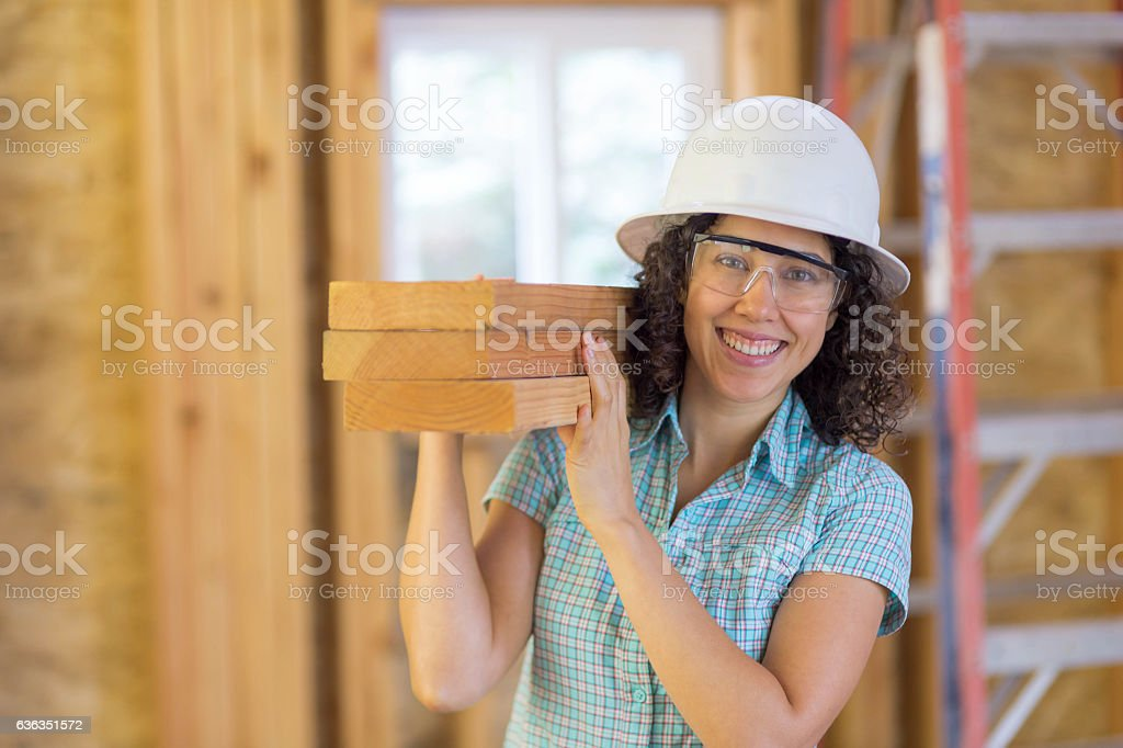 Attractive ethnic female carrying a stack of 2x4's stock photo