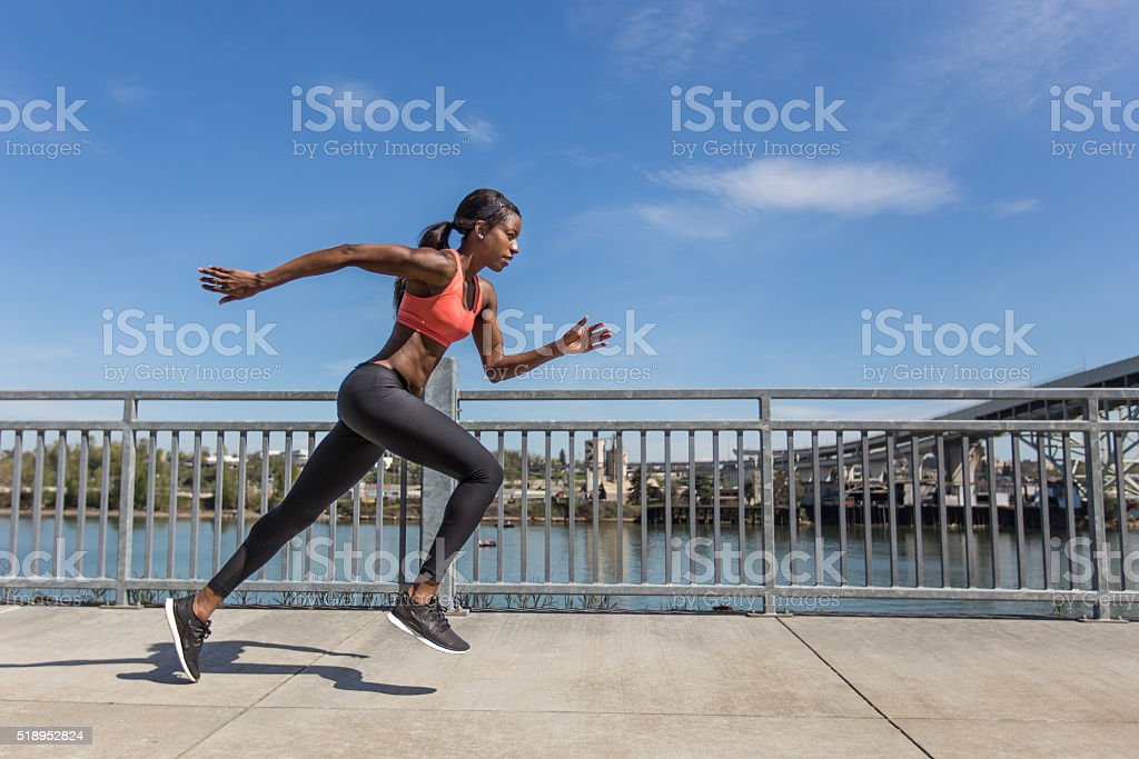 Attractive ethnic female sprinter training in the city stock photo