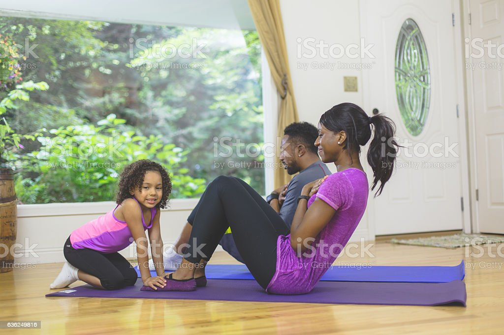 Attractive ethnic mother and father exercising at stock photo