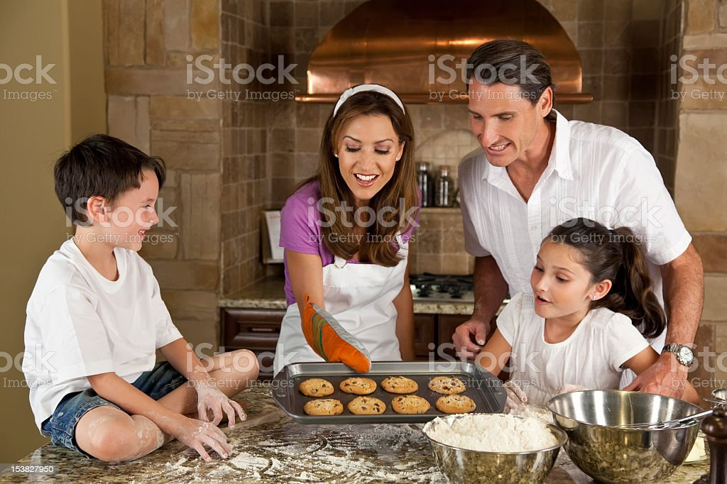 Attractive Family Baking and Eating Cookies In A Kitchen royalty-free stock photo