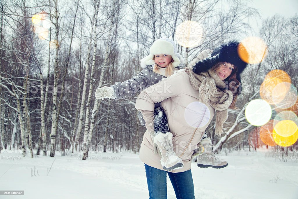 Attractive family mother and daughter having fun in winter park stock photo