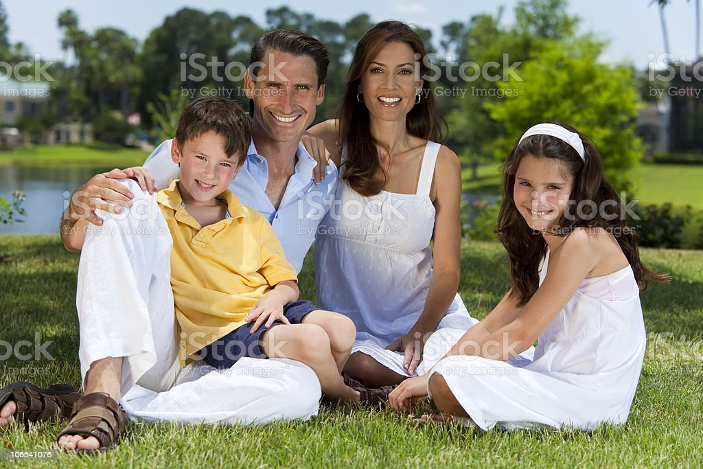 Attractive Family Sitting On Grass Outside In Sunshine royalty-free stock photo