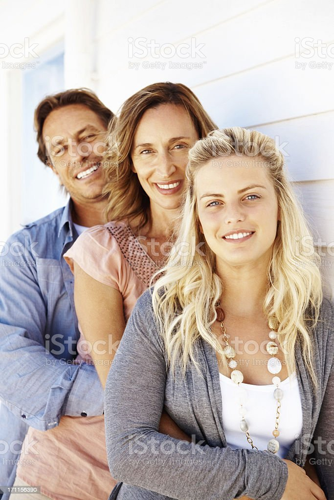 Attractive family standing in a row and embracing each other royalty-free stock photo