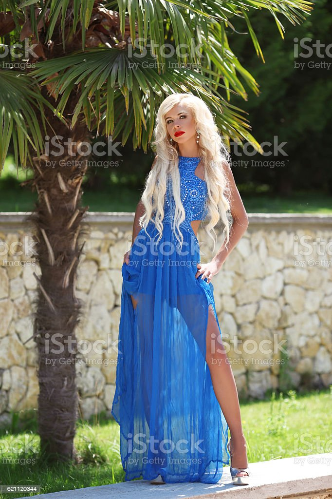 Attractive fashion blond woman model posing in blue long dress stock photo