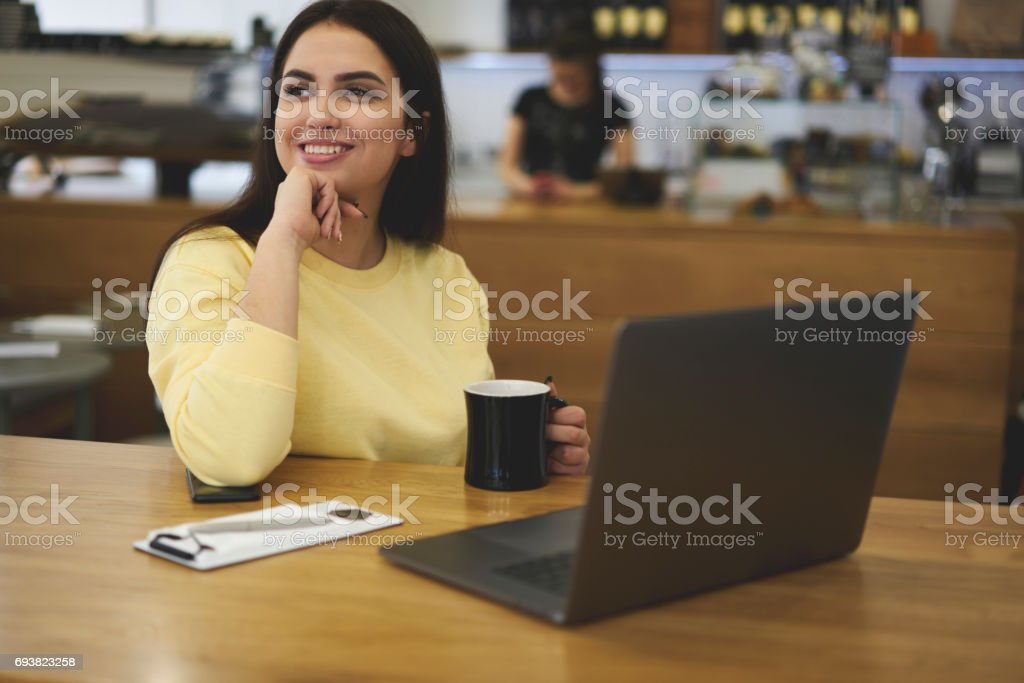 Attractive female administrative manager sitting at wooden table stock photo