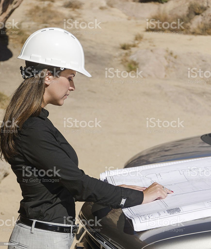 Attractive Female Architect reviewing Construction Plans stock photo