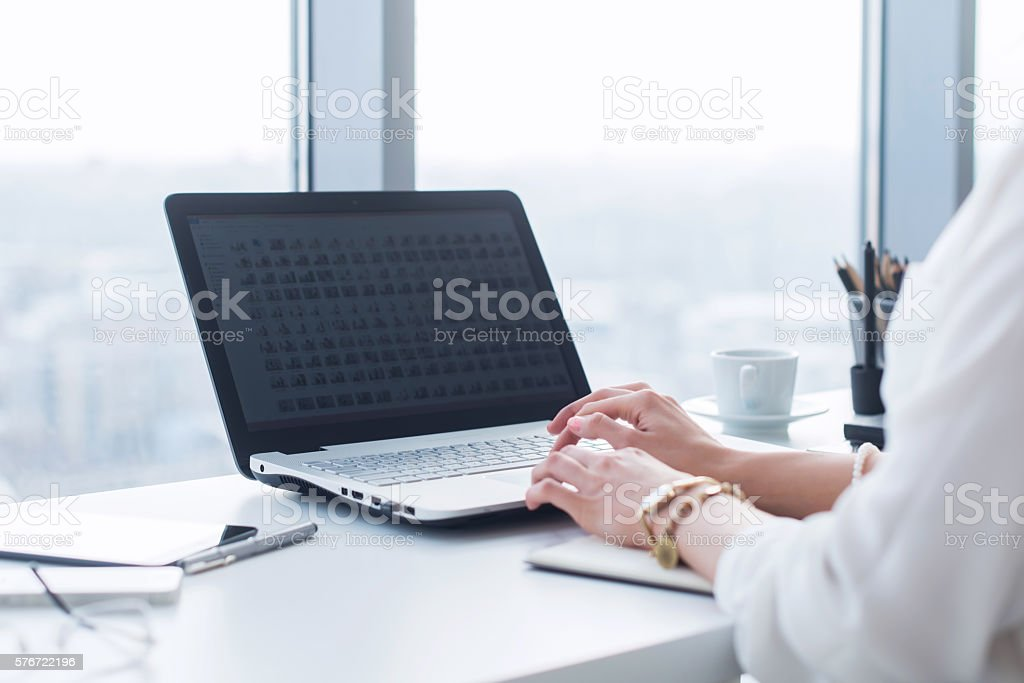 Attractive female assistant working, typing, using portable computer, concentrated, looking stock photo