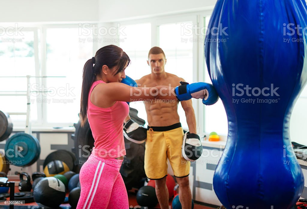 Attractive female athlete practices boxing on punching bag stock photo