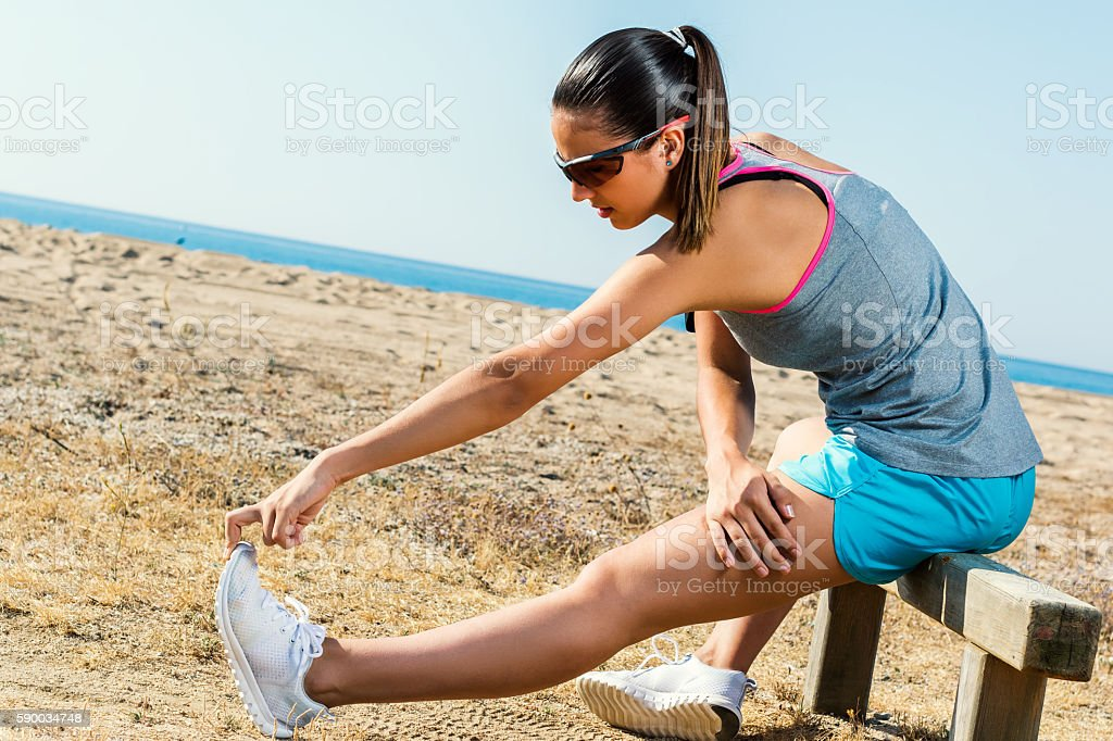Attractive female athlete stretching hamstrings outdoors. photo libre de droits