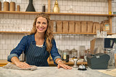 Attractive female barista making cup of coffee