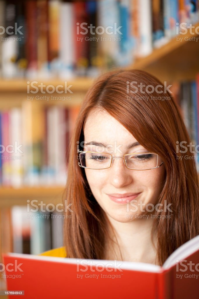 Attractive female reading book in library royalty-free stock photo