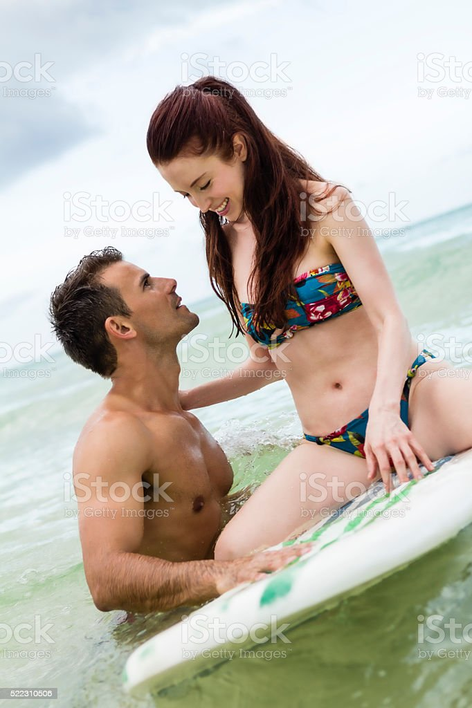 Attractive female sitting on surfboard with male standing stock photo