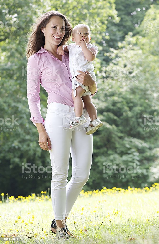 Attractive female smiling and holding baby in the park royalty-free stock photo