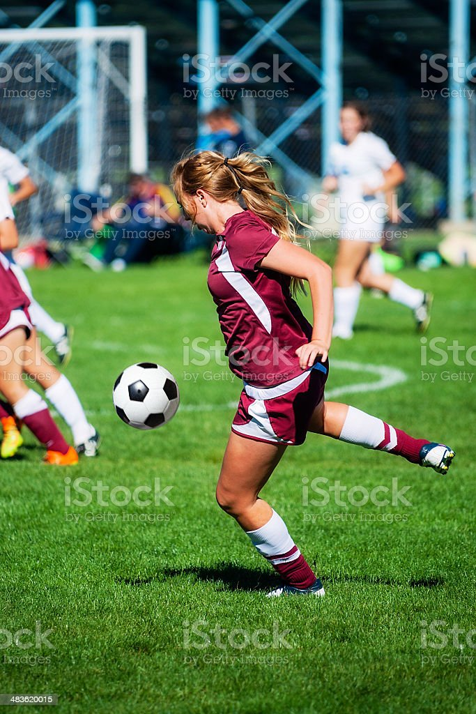 Attractive Female Soccer Player Concentrates on Airborne Ball royalty-free stock photo