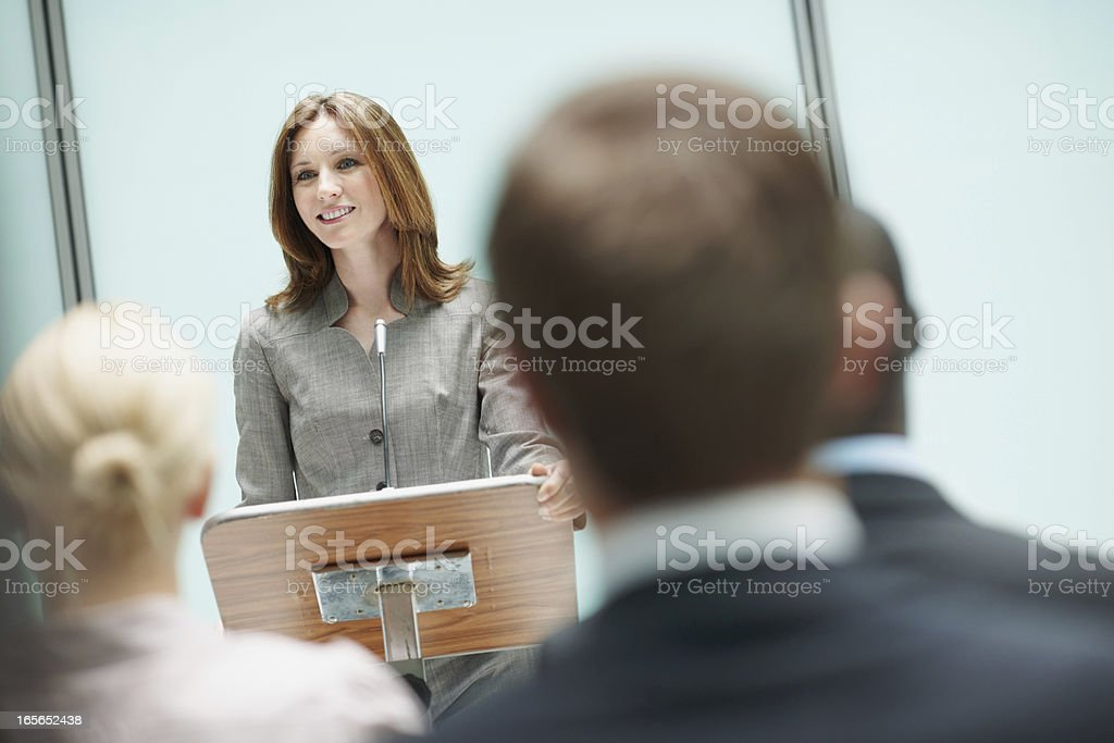Attractive female speaker at business seminar stock photo