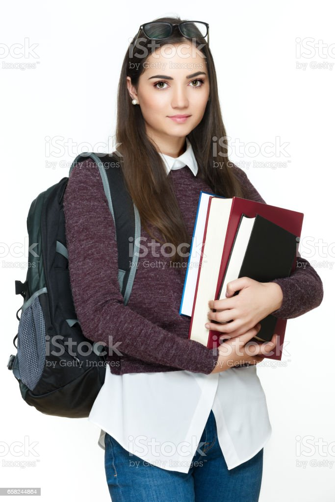 Attractive female student holding books, isolated on white background. stock photo
