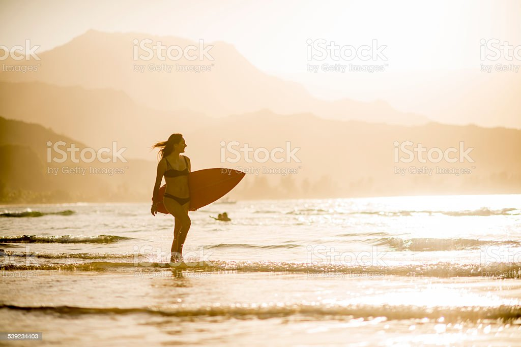 Attractive female surfer at the beach stock photo