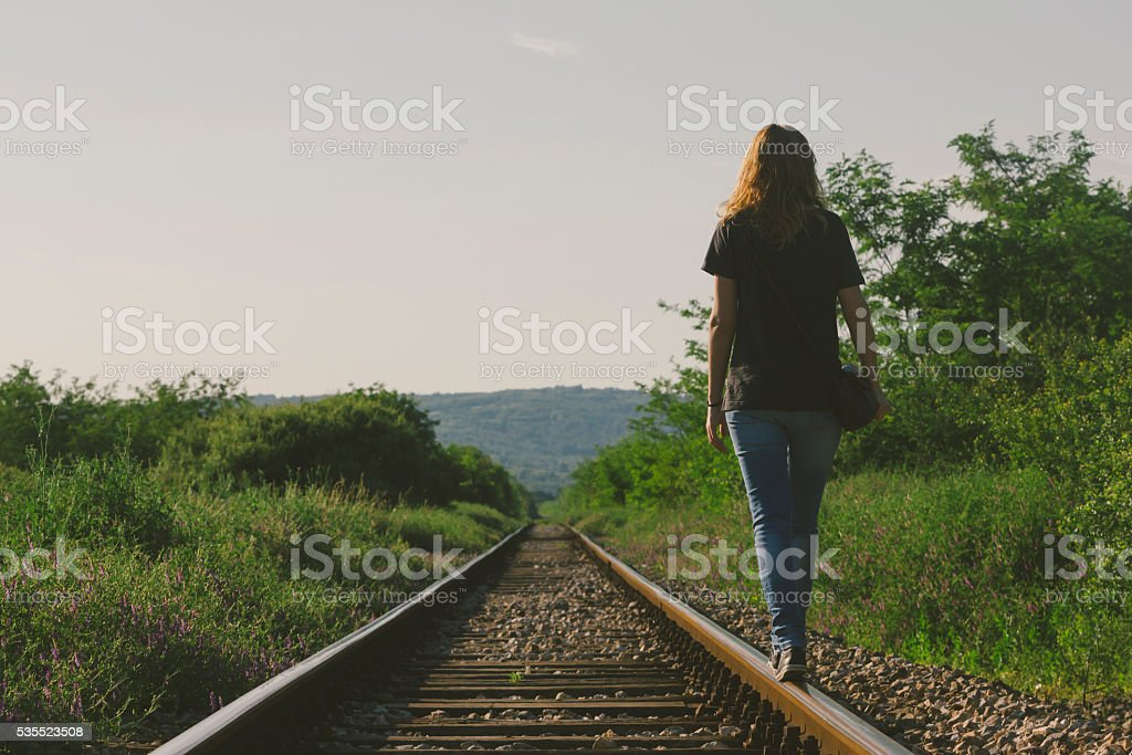 Attractive female walking down the railway in sunset stock photo