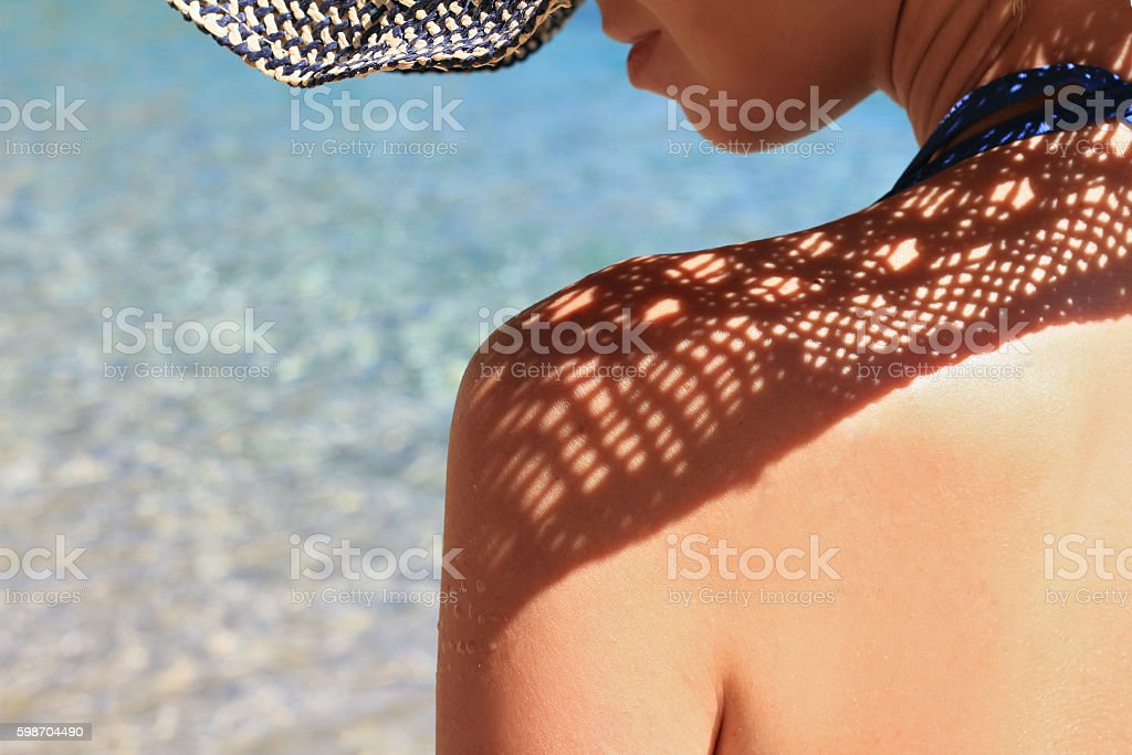 Attractive female wearing straw hat on the beach close up. Summer...