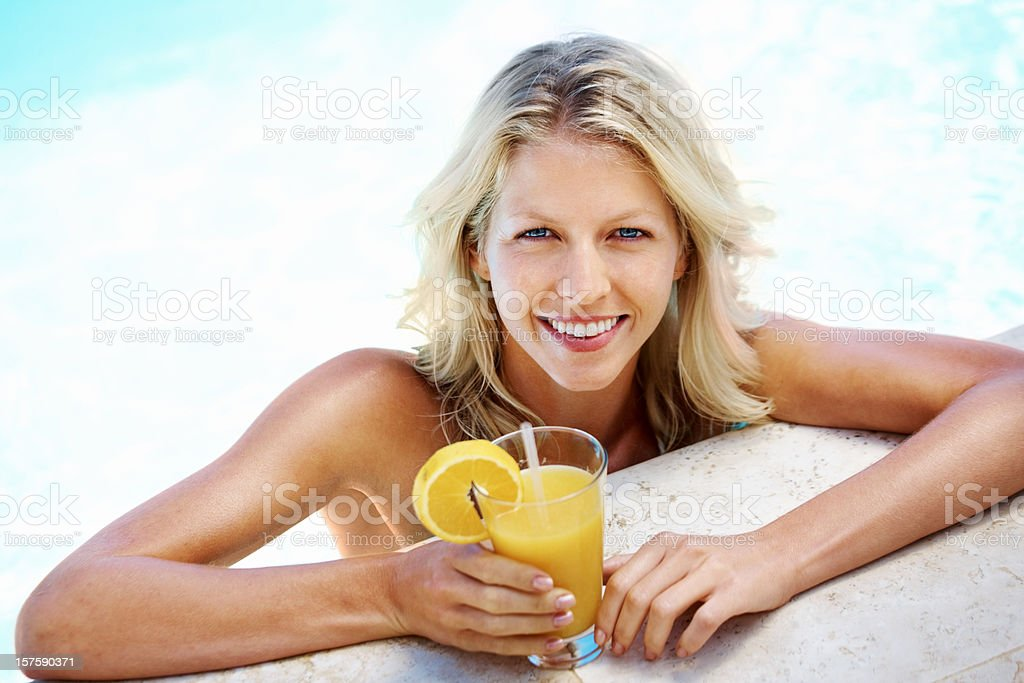 Attractive female with a glass of juice at pool stock photo