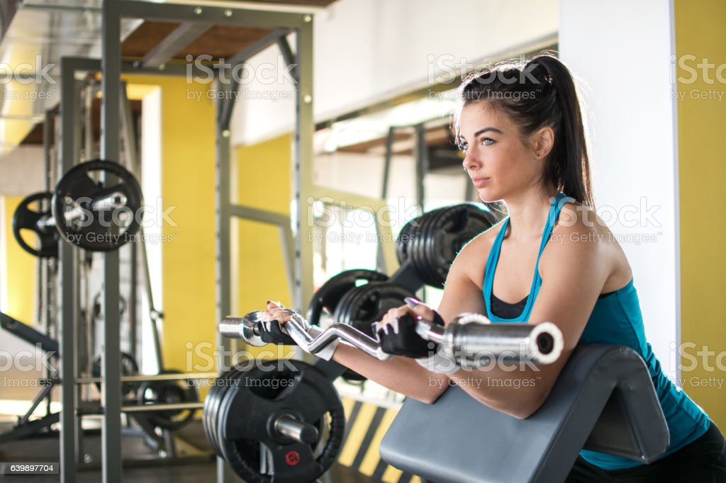 Attractive fit woman working out with curl bar in gym. stock photo