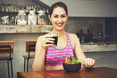 Attractive fitness woman is eating salad with healthy juice