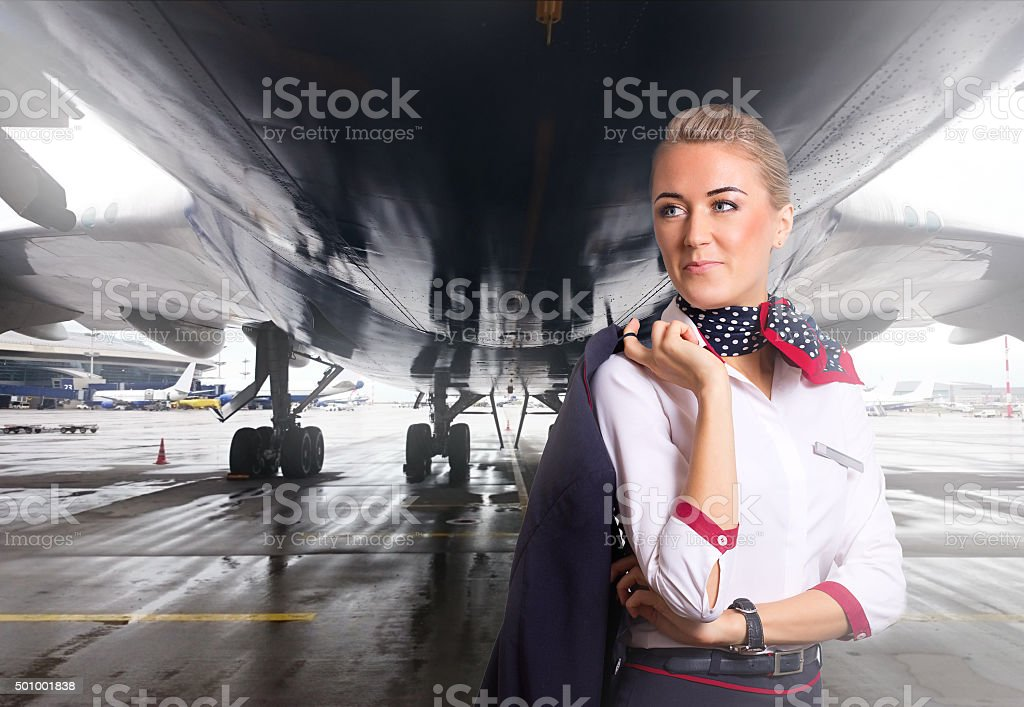 Attractive flight attendant near airplane in airport. stock photo