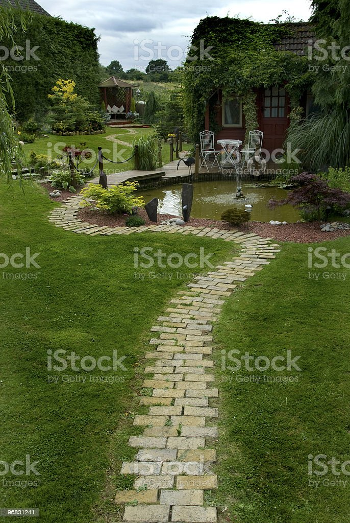 Attractive garden with winding path and pond royalty-free stock photo