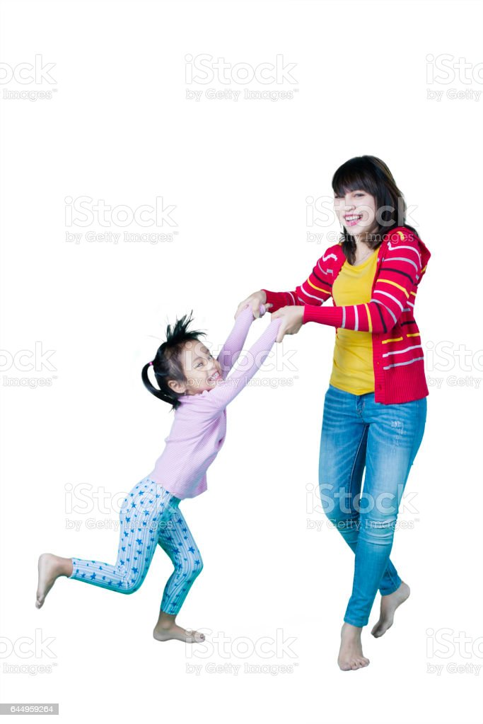 Attractive girl and mother playing in studio stock photo