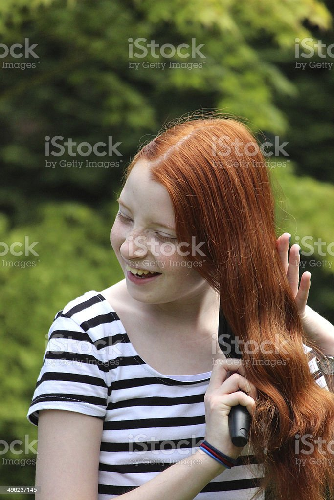Attractive girl brushing her long red hair outside in sunshine stock photo