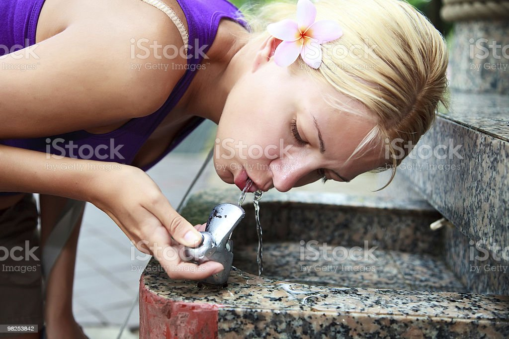 attractive girl drinking water from fountain stock photo