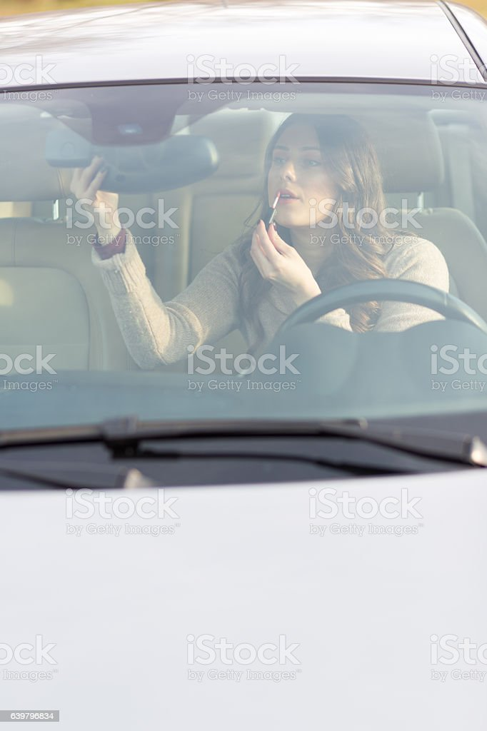 Attractive girl driving car, looking herself in rear view mirror stock photo