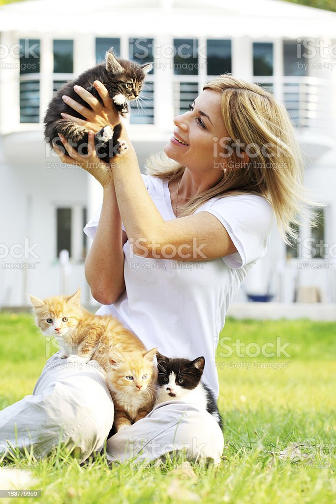 Attractive girl enjoys outdoor with little cats. royalty-free stock photo