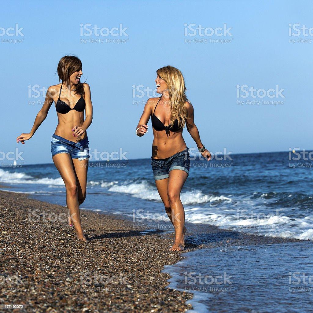 Jolie fille amis courir le long du bord de mer. photo libre de droits